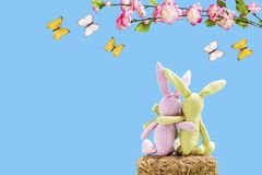 Two rabbits on a straw bale with flowers and butterflies. In front of a blue background Stock Photography