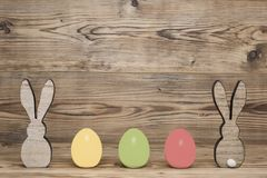 Two rabbits three colorful eggs. In front of a wood background stock photo