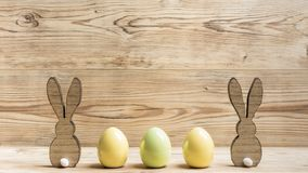 Two rabbits three eggs. In front of a wood background stock images