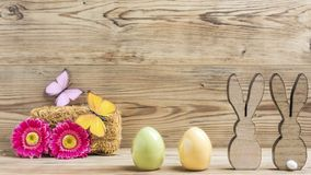 Two rabbits two eggs. With flowers and butterfly Royalty Free Stock Photography