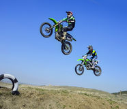 Two racers jumping in air during motocros competition. Against sky background stock images