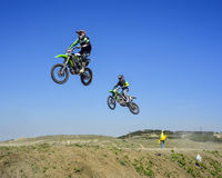 Two racers jumping in the air during motocros competition. Two racers jumping in air during motocros competition against sky background stock photos