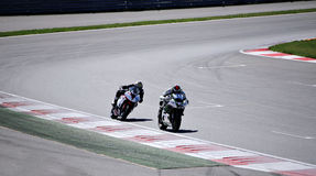Two racers on a motorcycles rides on the speed of the track Royalty Free Stock Image