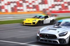 Two racing cars on a racing track. Two race cars racing at high speed on speed track with motion blur on a racing track on the background of the stands royalty free stock image