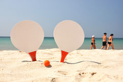 Two rackets and a ball on the beach Stock Photos