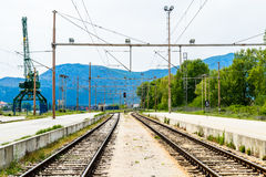 Two railroad tracks. With crane in the background. Industrial scenery Stock Photo