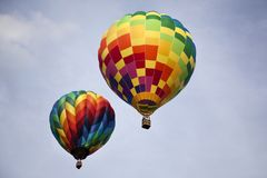 Two rainbow colored hot air balloons flying. Multi-colored hot air balloons inflated and soaring through the sky on a cloudy day Royalty Free Stock Images