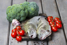 Two rainbow trouts, tomatoes and garlic Stock Image