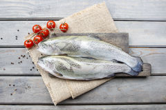 Two rainbow trouts and tomatoes on rustic wooden table. Healthy food royalty free stock image