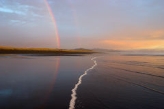 Two Rainbows. Reflected off a black sand beach, Tahahoma, New Zealand royalty free stock photography