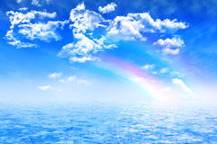 Two rainbows on blue sky with clouds, over ocean Royalty Free Stock Images