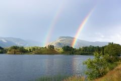 Two Rainbows. Landscape with two rainbows above the lake Stock Photos