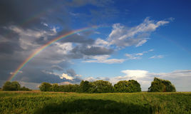 Two rainbows. Over green fields and trees Royalty Free Stock Photos