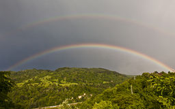 Two rainbows. Over green valley Royalty Free Stock Photos