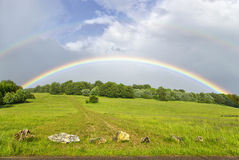 Two rainbows over hilly grassland Royalty Free Stock Image