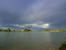 Two rainbows over lake Stock Photos