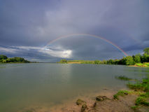 Two rainbows over lake Royalty Free Stock Photo
