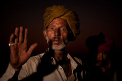 Two rajasthani men with turbans. Two rajasthani men with a dark red sky behind them. men at the Pushkar Camel Fair 2009 the arm is raised as greeting gesture Royalty Free Stock Photos