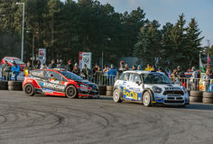 Two rally cars competing with crowd watching in the back Royalty Free Stock Image