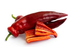 Two Ramiro sweet pointed peppers isolated on white and two cut p. Ieces without seeds royalty free stock photography