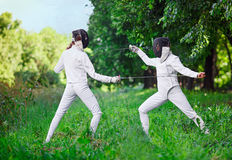 Two rapier fencer women fighting over beautiful nature Royalty Free Stock Image