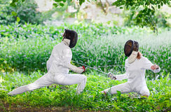 Two rapier fencer women fighting over beautiful nature Stock Photography