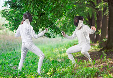 Two rapier fencer women fighting over beautiful nature Stock Photos