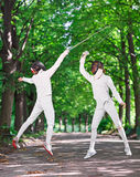 Two rapier fencer women fighting over park alley Royalty Free Stock Photos