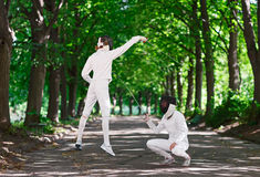 Two rapier fencer women fighting over park alley Royalty Free Stock Photography