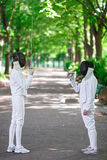 Two rapier fencers women staying in park alley Royalty Free Stock Images