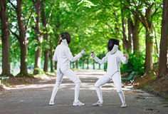 Two rapier fencers women staying in park alley Stock Photo
