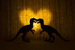 Two raptors - dinosaurs - in front of a glowing heart. stock images