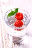 Two raspberries in glass with water and mint leaves Stock Images