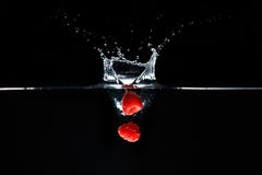 Two raspberrys falls deeply under water with a big splash. Royalty Free Stock Images