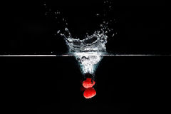 Two raspberrys falls deeply under water with a big splash. Royalty Free Stock Photos
