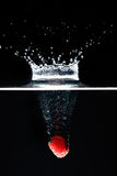 Two raspberrys falls deeply under water with a big splash. Royalty Free Stock Photography