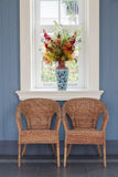 Two rattan chairs with vase and window Stock Photo