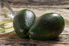 Two Raw Avocado with Bottle of Oil on Wood Background Stock Photos