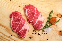 Two raw beef neck steak on wooden background stock photos