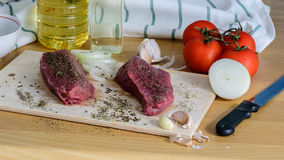 Two raw beef steak on a cutting board with spices ready for cooking. Raw beef steak on a cutting board with spices and vegetable Stock Photo