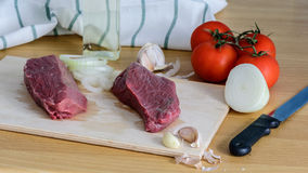 Two raw beef steak on a cutting board with spices. Raw beef steak on a cutting board with spices and vegetable Royalty Free Stock Image