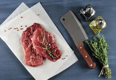 Two raw beef steak with spices, kitchen knife. On wooden background top view Stock Image