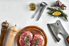 Two raw beef steak with spices on wooden board and kitchen ax on white background, top view. Copy space. Still life. Flat lay Stock Photos