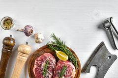 Two raw beef steak with spices on wooden board and kitchen ax on white background, top view. Copy space. Still life. Flat lay Royalty Free Stock Photo