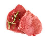 Two raw beef steaks. With rosemary isolated on white background Royalty Free Stock Images