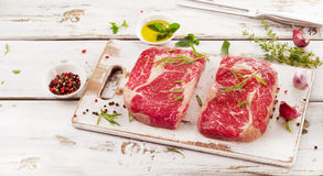 Two Raw Beef Steaks on  white wooden  board. Royalty Free Stock Photos