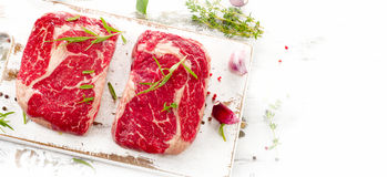Two Raw Beef Steaks on  a white wooden  board. Stock Photography