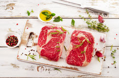 Two Raw Beef Steaks on  a wooden  board. Royalty Free Stock Photos
