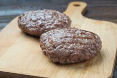 Two grilled hamburger patty on cutting board. Two raw burgers - cutlets from organic beef meat on rustic wood cutting board Royalty Free Stock Photos