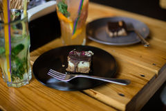 Two raw cakes with chocolate on black and grey plates with forks standing on wooden table. Near glasses of lemonade Royalty Free Stock Image